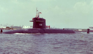 Submarine USS Tecumseh pulling into port with sailors on the sail and deck