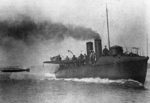A torpedo boat, with steam pouring from a steam stack, fires a torpedo
