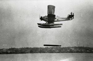 An historic aircraft drops a torpedo towards the water