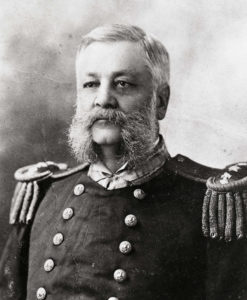 A 19th century portrait photograph of a middle aged man with large mutton chops in a Navy uniform