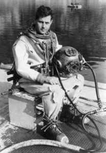 Navy diver sits on box while wearing a historic diving suit and holding a diving helmet in his lap