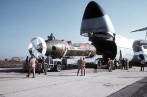 A DSRV on a trailer is pushed inside an aircraft hangar