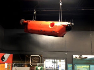 A large orange-red remotely operated vehicle is suspended from the ceiling of an exhibit gallery
