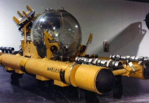 A large yellow submersible with a large clear acrylic pressure sphere sits in a museum exhibit gallery