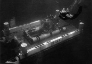 Black and white photograph of Makakai underwater sitting atop an underwater platform
