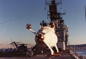 Tail end of a submersible faces camera, submersible is strapped to deck of a ship