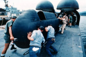 Sailors push a Mark 7 Mod 6 swimmer delivery vehicle on the deck of a submarine into a cylindrical deck chamber