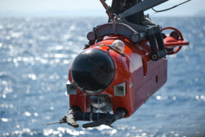 Front view of mine neutralization vehicle suspended over water. Vehicle is bright orange/red-colored with a hemispherical black dome on the nose.