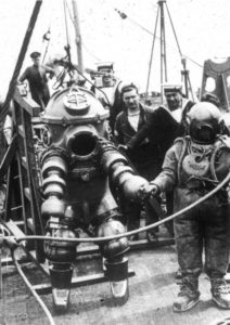 1930s mechanical diving suit on the deck of a ship