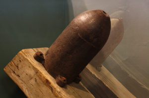 A Civil War era frame mine, which looks like a large artillery shell, is mounted on an angled wooden timber